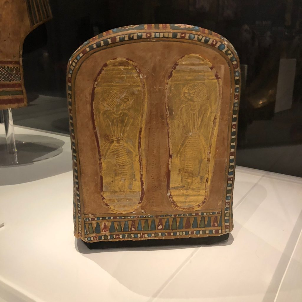Foot case detail showing gilded soles with depictions of foreigners