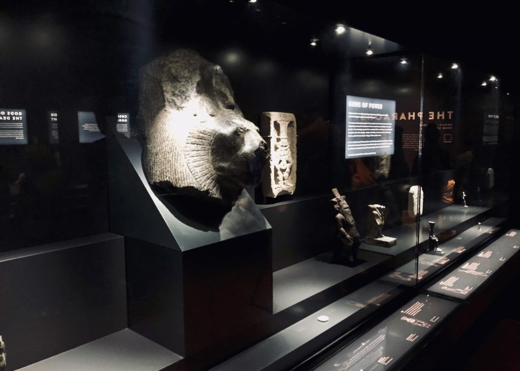 A large head of Sekhmet dominates the dark-lit display with other religious objects on the right (photo: Nile Scribes)